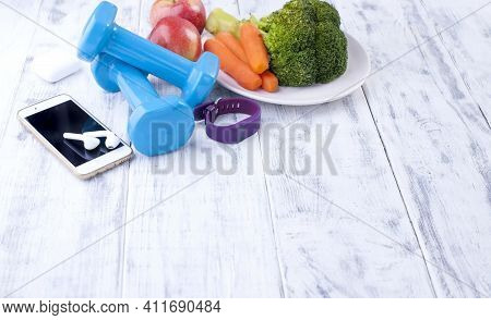 Fitness Concept With Dumbbells And Fresh Fruits And Vegetables. Sports Nutrition. Healthy Lifestyle