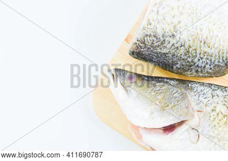 Barramundi Fish On Wooden Chopping Board Over White Background.