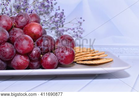 Bunch Of Grapes And Cracker On Plate. Still Life With Snack For Wine. Red Grapes On Beige Platter On