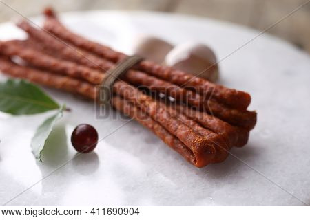 A Close-up Of Homemade, Smoked Kabanosy Sausage, Tied With String, On White Stony Cutting Board. Tra