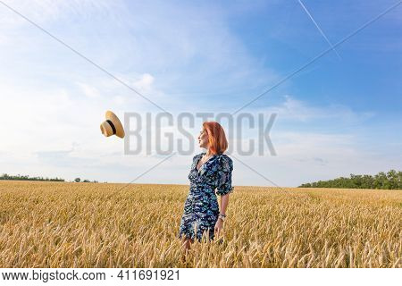 A Young Girl's Hat Flew Off In A Wheat Field. Windy Weather Concept.