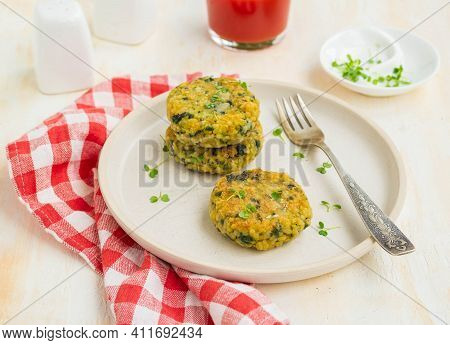 Fried Burgers Or Cutlets Of Bulgur, Carrots And Spinach On A Light Ceramic Plate On A Light Concrete