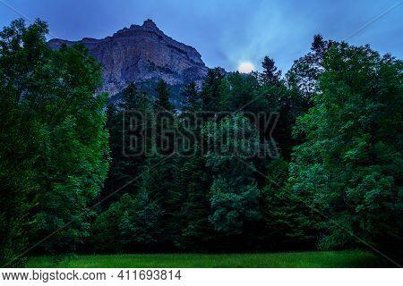 Dark Landscape With Mountain, Sun Or Moon, Green Grass Trees. Ordesa Pyrenees.