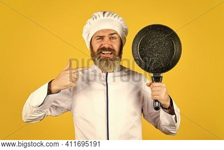 Professional Kitchenware. Bearded Chef Preparing Breakfast. Nonstick Pan For Frying. Enameled Cookin