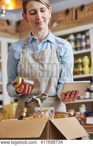 Female Owner Of Delicatessen Food Shop With Digital Tablet Preparing Online Grocery Order