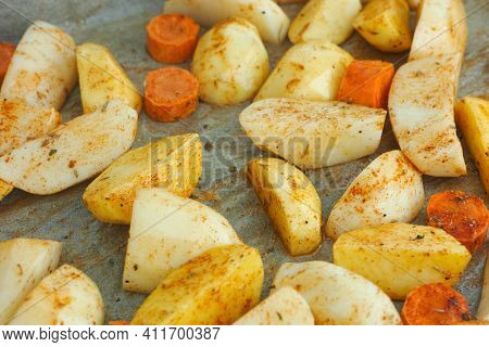 Peeled And Chopped Raw Potatoes And Carrots With Spice On A Baking Sheet. Close Up.