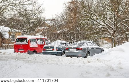 Lutsk, Ukraine - February 12, 2020: City Street After Blizzard. Stuck Car In Snow And Ice. Buried Ve