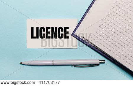 On A Light Blue Background, An Open Notebook, A White Pen And A Card With The Text Licence. View Fro