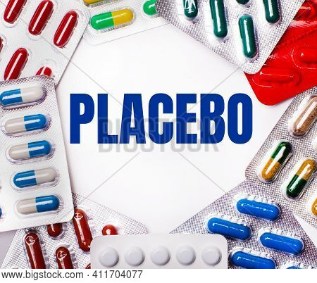 The Word Placebo Is Written On A Light Background Surrounded By Multi-colored Packages With Pills. M