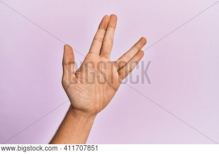 Arm and hand of caucasian young man over pink isolated background greeting doing vulcan salute, showing hand palm and fingers, freak culture