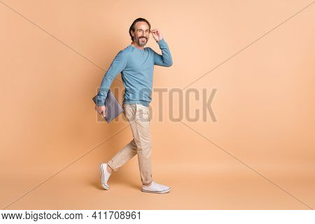 Full Length Profile Photo Of Man Walk Hold Laptop Wear Specs Blue Sweater Pants Sneakers Isolated Be