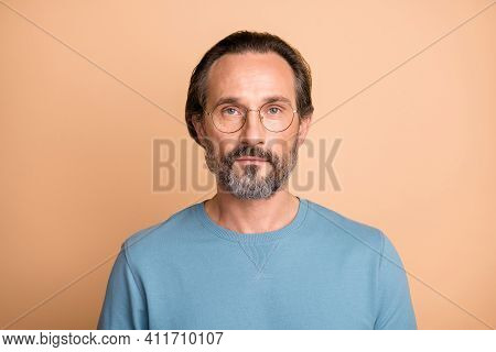 Photo Of Serious Calm Mature Guy Look Camera Wear Eyeglasses Blue Pullover Isolated Beige Color Back