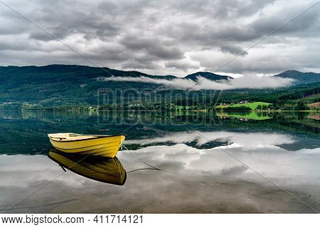 A Single Yellow Row Boat Floats In A Perfectly Calm Lake Which Creates A Beautiful Reflection Of The