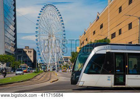 Rio De Janeiro, Brazil - January 7, 2021: Vlt Tram Is Passing In Front Of The Rio Star Ferris Wheel