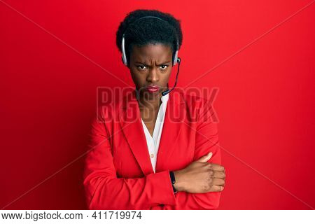 Young african american girl wearing call center agent headset skeptic and nervous, disapproving expression on face with crossed arms. negative person.
