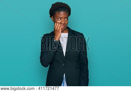 Young african american girl wearing business clothes looking stressed and nervous with hands on mouth biting nails. anxiety problem.