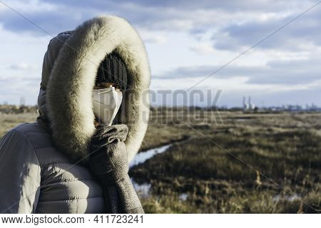 Worried Woman  Wearing A Protective Face Mask And Winter Clothes With Grassland Wilderness And Facto