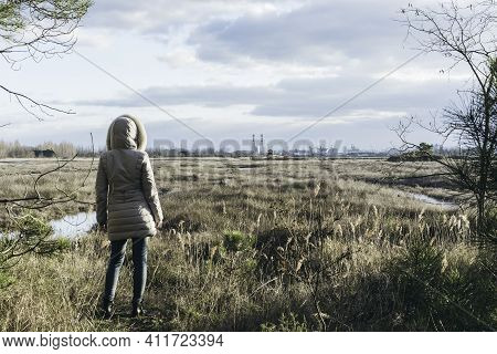 Back View Of Woman Wearing Winter Clothes In Front Of Grassland Wilderness And Factories On The Hori