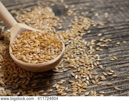 Golden Flax Seeds, Flaxseed In A Wooden Spoon On An Old Rustic Background Close-up, White Flax