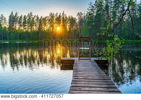 Amazing Northern Landscape Of Lake And Forest In Summer Evening At Sunset With Chair On Wooden Plank