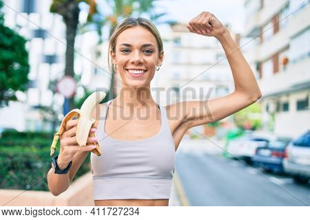Young cauciasian fitness woman wearing sport clothes training outdoors eating healthy banana and showing proud arm muscle