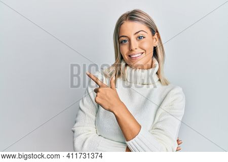 Beautiful blonde woman wearing casual turtleneck sweater smiling cheerful pointing with hand and finger up to the side