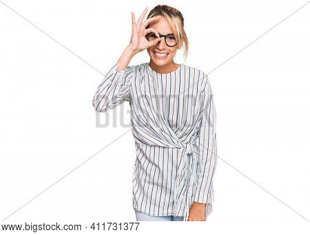 Beautiful blonde woman wearing business shirt and glasses doing ok gesture with hand smiling, eye looking through fingers with happy face.
