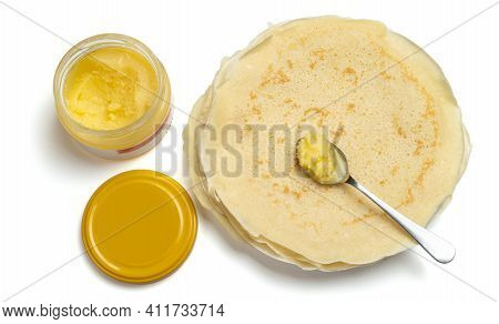 A Spoonful Of Ghee Lies On A Plate Of Pancakes Next To An Open Glass Jar Of Ghee. Isolated On A Whit