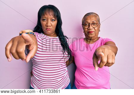 Hispanic family of mother and daughter hugging together with love pointing with finger to the camera and to you, confident gesture looking serious