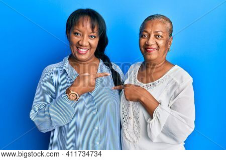 Hispanic family of mother and daughter hugging together with love smiling happy pointing with hand and finger