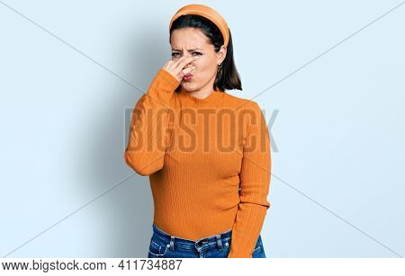 Young hispanic girl wearing casual white t shirt smelling something stinky and disgusting, intolerable smell, holding breath with fingers on nose. bad smell
