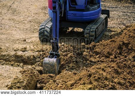Excavation A Trench For The Foundation. Ground In Backhoe Dump Bucket For Earthmoving Works In Const