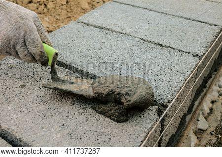 Sealing Masonry Seams With Cement Mortar. Bricklayer Lays A Wall Of Heavy Concrete Blocks.