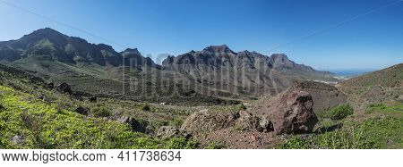 Panoramic View Of Rocky Mountains And Green Valley With Big Red Rock. Landscape In The North West Of
