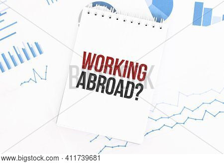 White Notepad With Text Working Abroad On The Financial Documentation. Finance And Business Concept