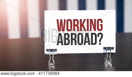 Working Abroad Sign On Paper On Dark Desk In Sunlight. Blue And White Background