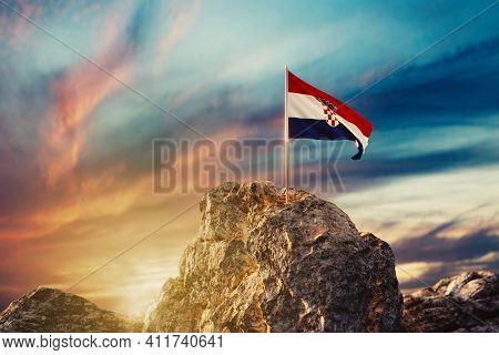 3d Rendering Of Waving Croatian Flag On Rocky Landscape In The Evening Sunlight