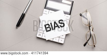 Pen, Calculator And Glasses On Grey Background. Business Concept. White Paper Sheet With Bias Sign