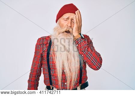 Old senior man with grey hair and long beard wearing hipster look with wool cap yawning tired covering half face, eye and mouth with hand. face hurts in pain.
