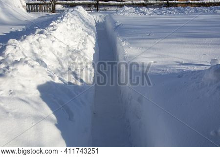 Ragging Snow Paths In The Garden In Winter. High Snowdrifts In The Country. Snowy Vegetable Garden I