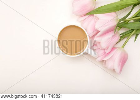 Morning Cup Of Coffee And Pink Flowers On White Table Top View. Flat Lay. Creative Breakfast Concept