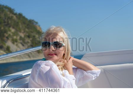 Blonde In A Dark Glasses Poses On A White Yacht