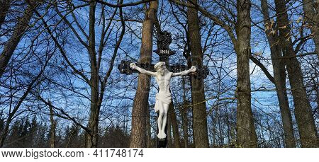 Cross And Jesus Christ Statue On Forest Background. Religious Symbol. Catholicism And Christianity C