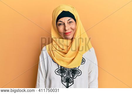 Middle age hispanic woman wearing traditional islamic hijab scarf relaxed with serious expression on face. simple and natural looking at the camera.
