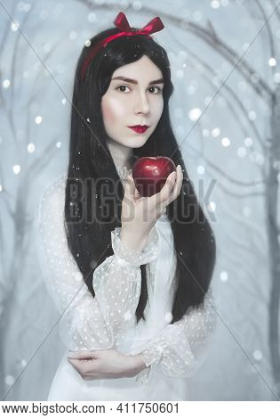 Young Pretty Woman With White Skin And Red Lips Is Keeping The Red Poisoned Apple.snow White Princes