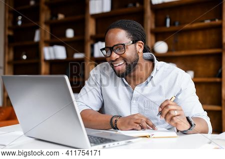 Smiling African-american Guy Takes Notes Watching Webinars On The Laptop, Researching Business Tasks