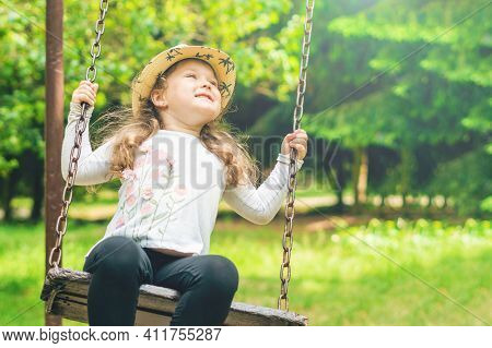 Child Playing In The Open Playground, Little Happy Laughing Girl Swinging On A Swing