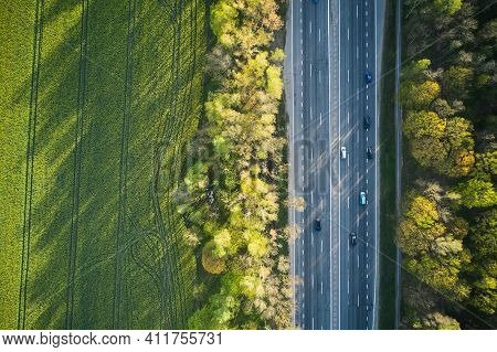 Aerial View Of Cars Driving Through The Green Forest On Highway.