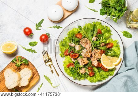 Salad With Baked Salmon Fish. Green Salad Mix With Tomatoes And Salmon. Top View At White Table.