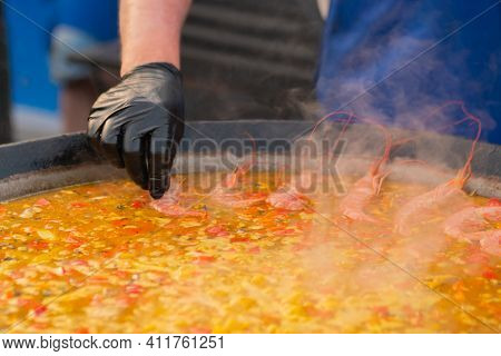 Chef Hand Cooking Yellow Paella With Shrimp, Mussel, Rice, Tomato, Saffron In Huge Paella Pan At Sum